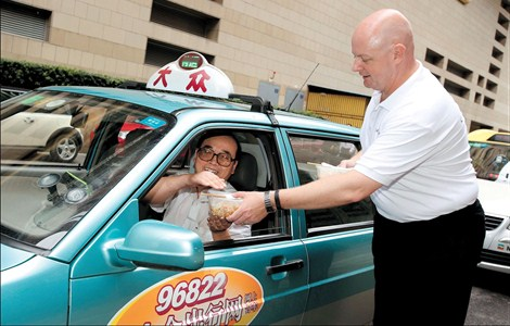 Peter Clarke, general manager of Pudong Shangri-La, East Shanghai, offers noodles to a taxi driver outside the hotel yesterday, the 16th anniversary of the hotel opening in Shanghai. To celebrate the occasion, Clarke and hotel employees gave away 1,600 bowls of noodles to taxi drivers outside the hotel to thank them for helping serve the guests. In China, eating noodles is one of the must-do things to celebrate a birthday. — Wang Rongjiang