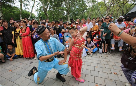 A man and a girl wearing folk costumes pose for a photo after a dance in Shanghai's Luxun Park, which reopened today after it was closed 12 months for renovations. The reopening attracted various groups of people who rushed in to do their morning exercises. –Zhang Suoqing