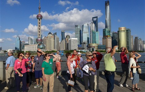 A group of foreign tourists on the Bund gaze up at the rare sight of white clouds in a clear blue sky yesterday as summer begins to give way to autumn. The new season is just around the corner with temperatures currently hovering between 23 and 28 degrees Celsius. An overcast sky with showers is forecast for today, with drizzle tomorrow and heavy rain on Thursday. — Wang Rongjiang
