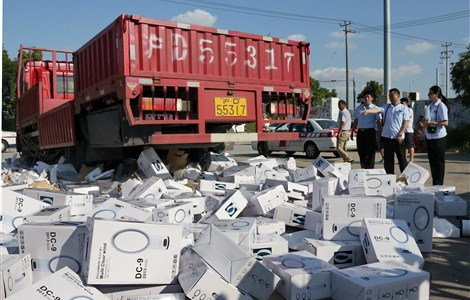 A truck crushes a large pile of bladeless fans yesterday in Shanghai's pilot free trade zone. The goods infringed the intellectual property rights of Britain's Dyson Ltd. — Ti Gong