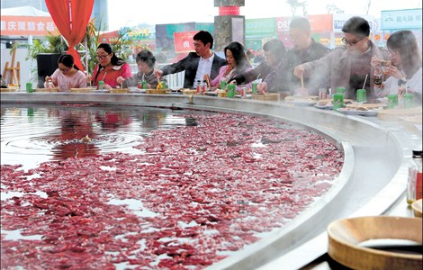 People tuck into a huge hotpot yesterday during the Hotpot Culture Festival in southwest China's Chongqing. The pot used to cook the massive meal was more than 1 meter deep, had a diameter of 10m, weighed 31 tons and was large enough to accommodate 56 diners simultaneously.