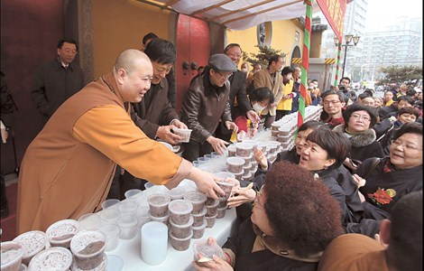 """Abbot Juexing distributes hot Laba congee, usually made from grain, red dates, nuts and raisins, at the Jade Buddha Temple yesterday. """"Laba"""" means the eighth day of the 12th lunar month, which was yesterday."""