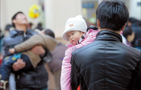 A father and child in Shanghai. Couples are being encouraged to have a second child.