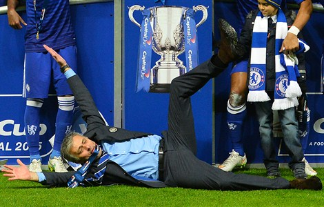 Chelsea's Portuguese manager Jose Mourinho celebrates on the floor as Chelsea players celebrate with the trophy during the presentation after Chelsea won the League Cup final football match against Tottenham Hotspur at Wembley Stadium in London on March 1, 2015. Chelsea won 2-0.