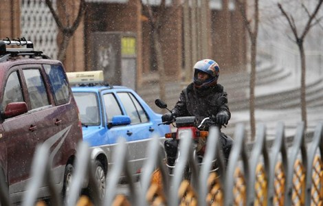 A resident rides a motorcycle in snow in Dongxian Autonomous County, northwest China's Gansu Province, April 18, 2015. Parts of Gansu witnessed snowfalls and a sudden drop in temperature on Saturday.
