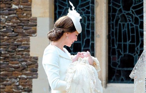 Britain's Catherine, Duchess of Cambridge, carries her daughter, Princess Charlotte of Cambridge, after taking her out of a pram as they arrive for Charlotte's christening at St Mary Magdalene Church in Sandringham, England, yesterday. Crowds gathered outside Queen Elizabeth II's country residence to catch a glimpse of the royal baby.