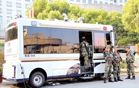 Armed police officers stand guard yesterday at a newly deployed police vehicle in downtown. Fifteen police vans kitted out as mobile command centers have been introduced in business areas and tourist spots in Huangpu District.