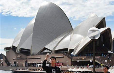 A tourist takes a 'selfie' in front of the Sydney Opera House on September 2, 2015, as data showed a boom in cashed-up visitors from China and India has helped Australia to its strongest tourism year since the Sydney Olympics, with more than Aus$33 billion (US$23.1 billion) pumped into the economy. The government-run Tourism Research Australia's International Visitor Survey showed that seven percent more people made the trip in the year to June 30 to reach a new high of 6.6 million -- the best since the hugely successful Games were held in 2000.
