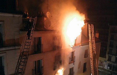 Firefighter battle flames during a fire at an apartment building in the north of Paris early on September 2, 2015. A fire in an apartment building in northern Paris early on September 2 that killed eight people, including two children, might have been started intentionally, officials said.