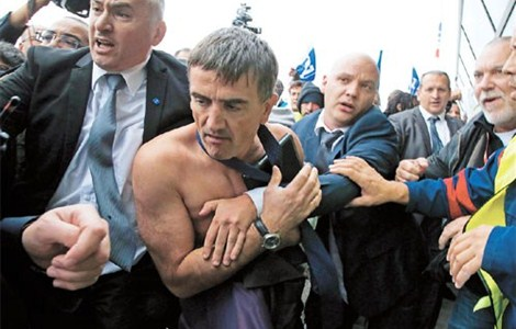 A shirtless Xavier Broseta (second left), executive vice president for human resources and labor relations at Air France, is escorted out by security after employees interrupted a meeting with representatives staff at the Air France headquarters in Roissy, near Paris, yesterday. — Reuters