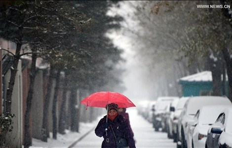 A woman walks in snow in Shenyang, capital of northeast China's Liaoning Province, Nov. 29.