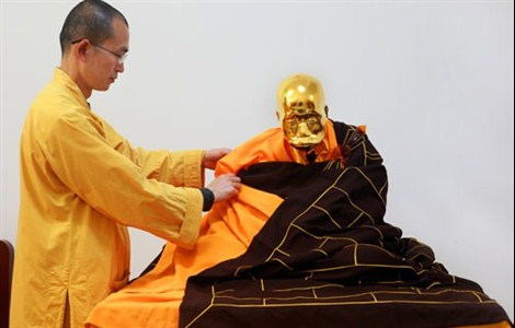 Puzhao Temple Abbot Zhenyu puts a kasaya on the mummified Fu Hou, who was also covered in gold leaf. — CFP