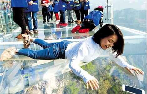 A woman gets a bird's eye view of Shilinxia scenic spot from a glass sightseeing platform in Pinggu District, Beijing, on Saturday. The platform, which juts out from the side of a cliff, is about 33 meters in length and covers 415 square meters.