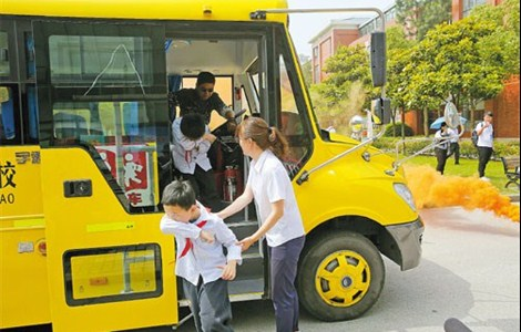 "Students from Xiwai International School are ""evacuated"" from a school bus during a fire drill yesterday in Songjiang District jointly conducted by the Shanghai education commission and Shanghai Traffic Police to teach them how to react in emergencies. — Zhang Suoqing"