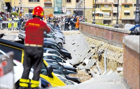 Damaged cars along the Arno River where the embankment collapsed early yesterday in central Florence. An underground water main break along Florence's picturesque Arno River has created a 200-meter-long sinkhole that buried dozens of parked cars.