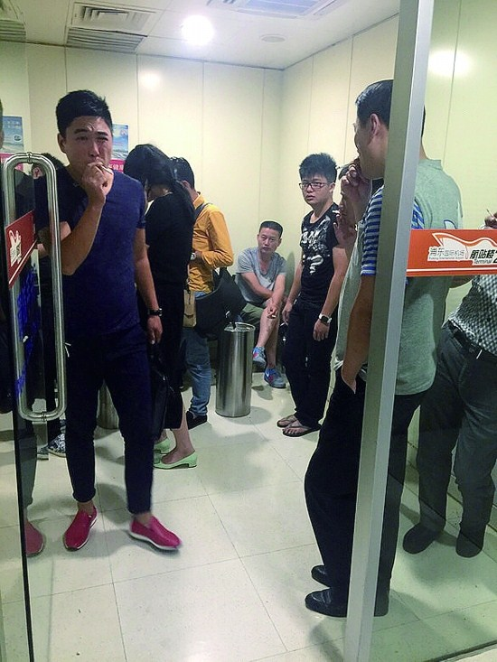 People smoke inside the designated room at Pudong Airport this May. The airport authority has said it plans to remove the designated smoking areas at Hongqiao and Pudong international airports.