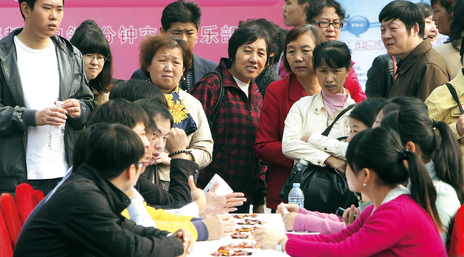 Anxious Chinese parents look on as their children participate in a speed dating event in Shanghai. — Wang Rongjiang