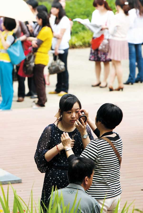 A mother helps her daughter with her makeup prior to a matchmaking event in Shanghai. In the background are hundreds of women lining up. — Wang Rongjiang