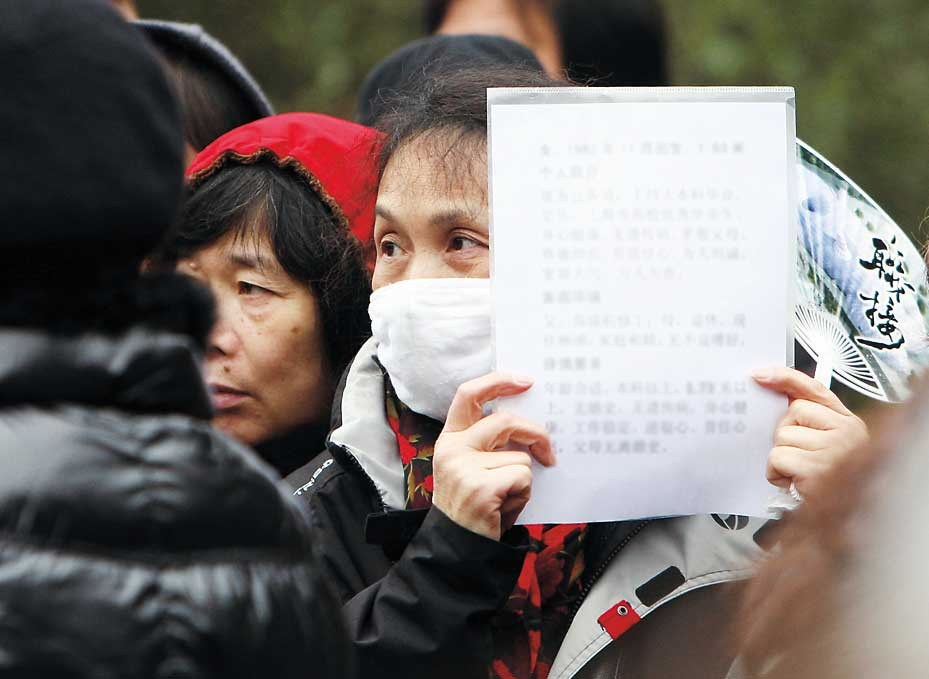 A mother displays a piece of paper bearing information about her daughter at a matchmaking event in Shanghai. — Wang Rongjiang