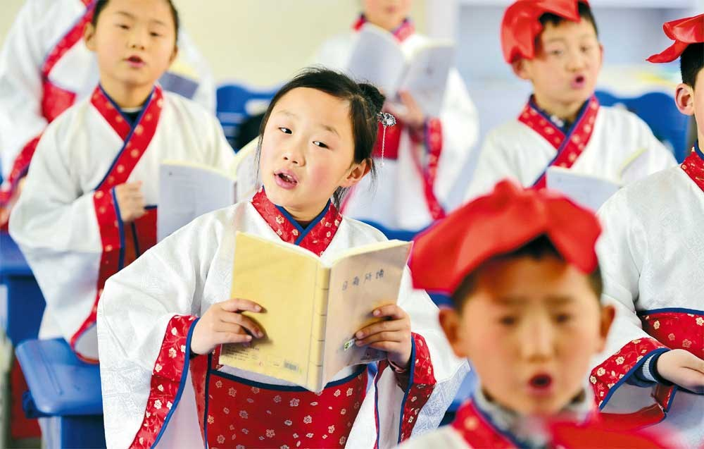 Dressed in traditional outfits, students at a primary school in Anhui Province recite ancient poems on the first day back to school on Monday after the winter holiday. — Xinhua