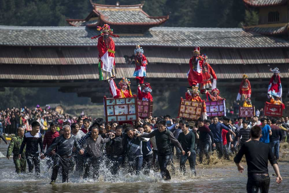 Locals carry children in palanquins during a festival through a river in Luofang Village in Fujian Province. The ceremonies accompanied the Lantern Festival but whose run-up and aftermath are marked by Hakka observances in Fujian.— AFP