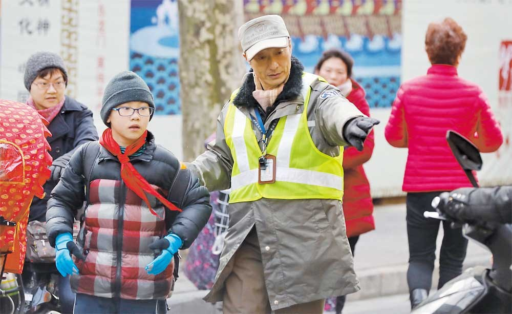 A traffic assistant helps a pupil cross a busy road to enter Luwan No. 1 Central Primary School yesterday. About 5,000 traffic police officers and traffic assistants helped to secure a successful first school day for pupils around the city. — Dong Jun
