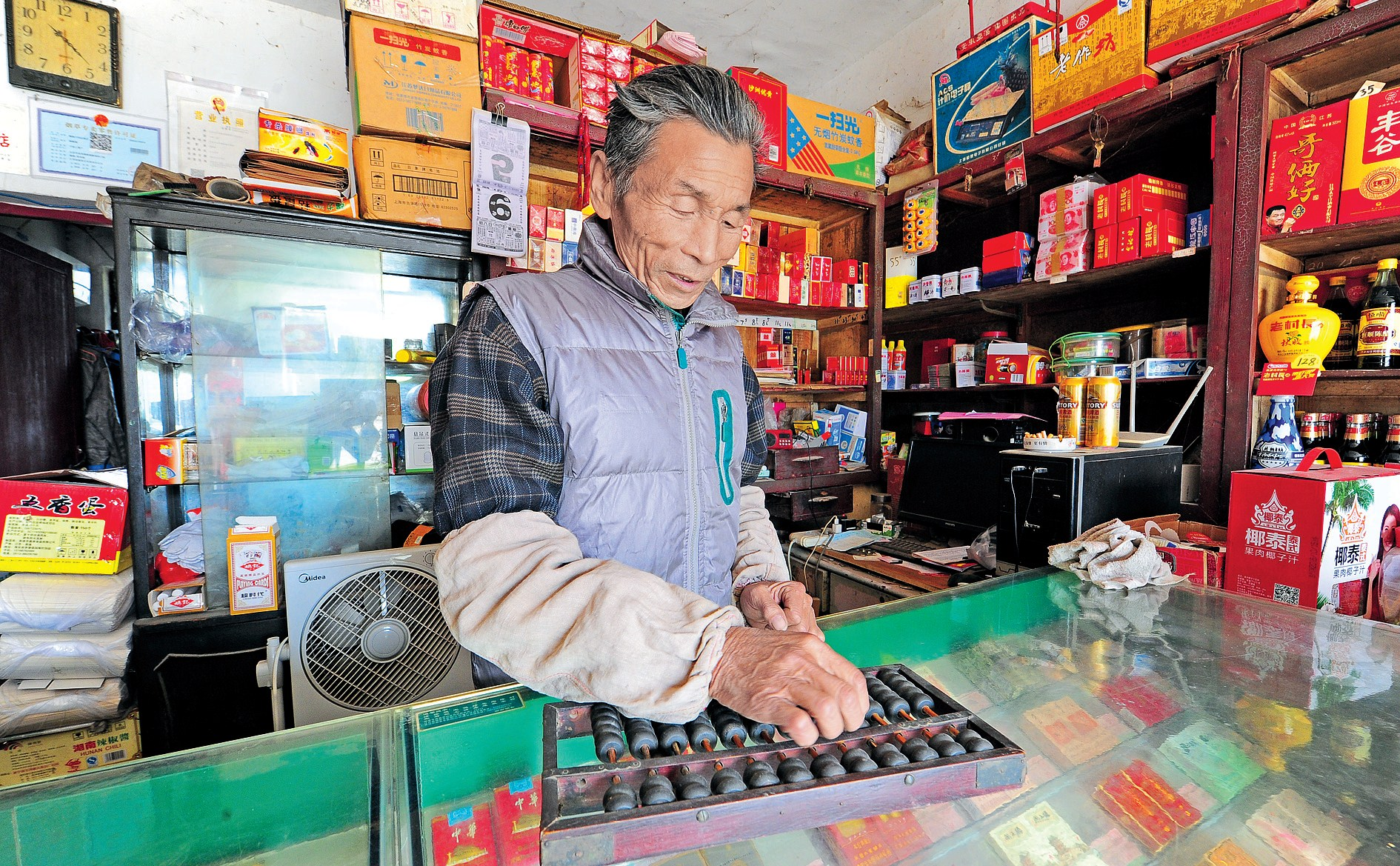 Guo Genfu, 70, uses a suanpan or an abacus in a convenience store which he has run for 48 years in Xinchuang village of Taicang City in Jiangsu Province. Guo still keeps the old habit of calculate with a suanpan when doing business. — IC