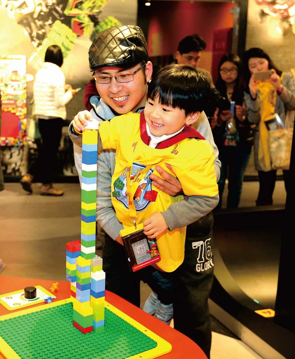 A dad plays with his son at the Legoland Discovery Center in Shanghai. Fathers are more than breadwinners. — Wang Rongjiang