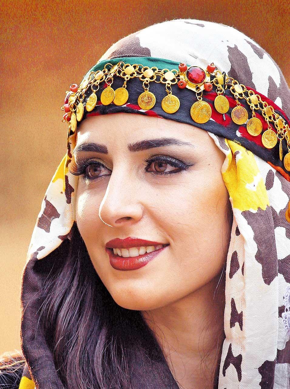 Efin Hissu, a Syrian-Kurdish woman, displays a range of traditional Kurdish attire. — AFP