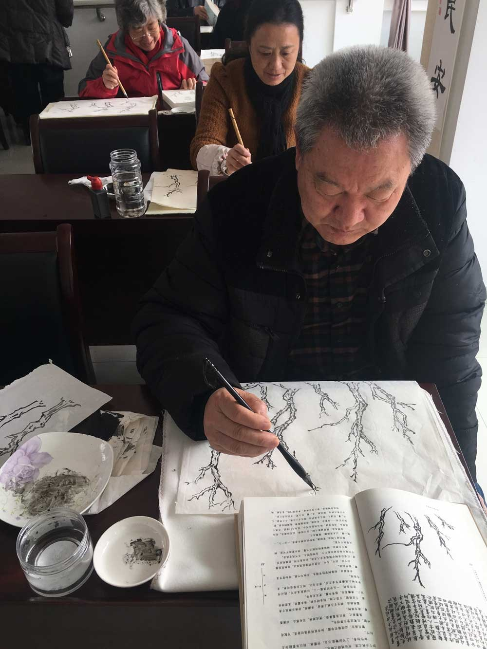 Huang Taosheng (front) and other seniors learn the basics of ink-wash paintings.