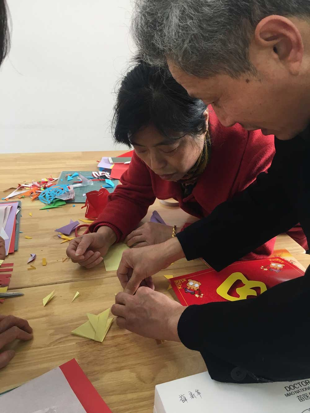 Wen Shixiong (right) teaches a student paper-cutting skills at the Jingjiang Senior Citizen School.