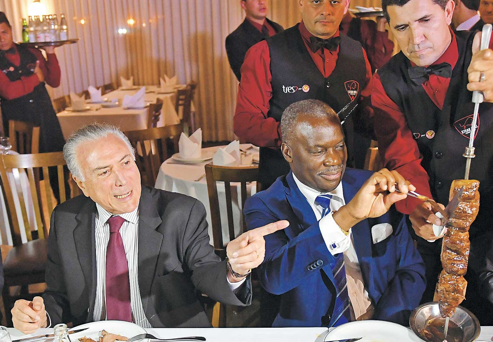 Brazilian President Michel Temer (left) and Angola's ambassador Nelson Manuel Cosme eat barbecue in a steak house in Brasilia on March 19 after a meeting with ambassadors from countries that import Brazilian meat after the scandal over tainted meat exports. — AFP