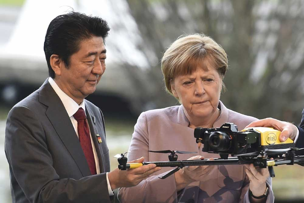 German Chancellor Angela Merkel and Japanese Prime Minister Shinzo Abe hold a drone during a media tour of the world's biggest computer and software fair, CeBit, in Hanover yesterday. The CeBit, with Japan as partner country, runs from yesterday until Friday. — Reuters