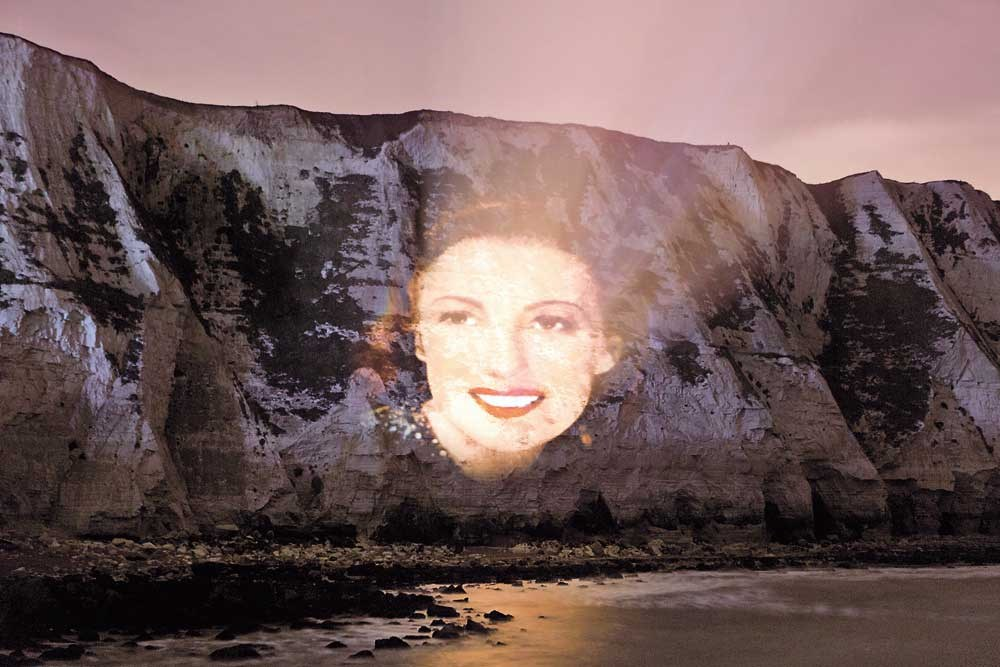 "A projection wishing singer and war time sweetheart Vera Lynn a happy birthday is projected on to the cliffs at Dover, Britain, yesterday. Vera Lynn, who entertained British troops during World War II with songs that captured a longing for home and peace, was honored on her 100th birthday yesterday with her image projected onto the iconic White Cliffs of Dover. Known as the Forces' Sweetheart, Lynn struck a chord with soldiers fighting overseas and with the public back in Britain with ""We'll Meet Again"" and other songs that gave voice to many Britons' hopes and fears about the conflict with Nazi Germany. — Reuters"