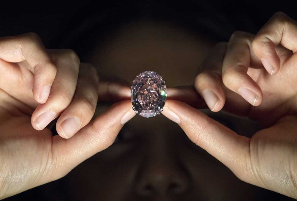 "A model poses with a 59.60-carat oval mixed-cut pink diamond, known as ""The Pink Star,"" during a photocall at Sotheby's auction house in London yesterday, to promote its forthcoming auction. The diamond, with an estimated value of 48.5 million pounds (US$60 million), is said to be the largest internally flawless fancy vivid pink diamond that the Gemological Institute of America has ever graded, and is set to be auctioned in Hong Kong on April 4. — AFP"
