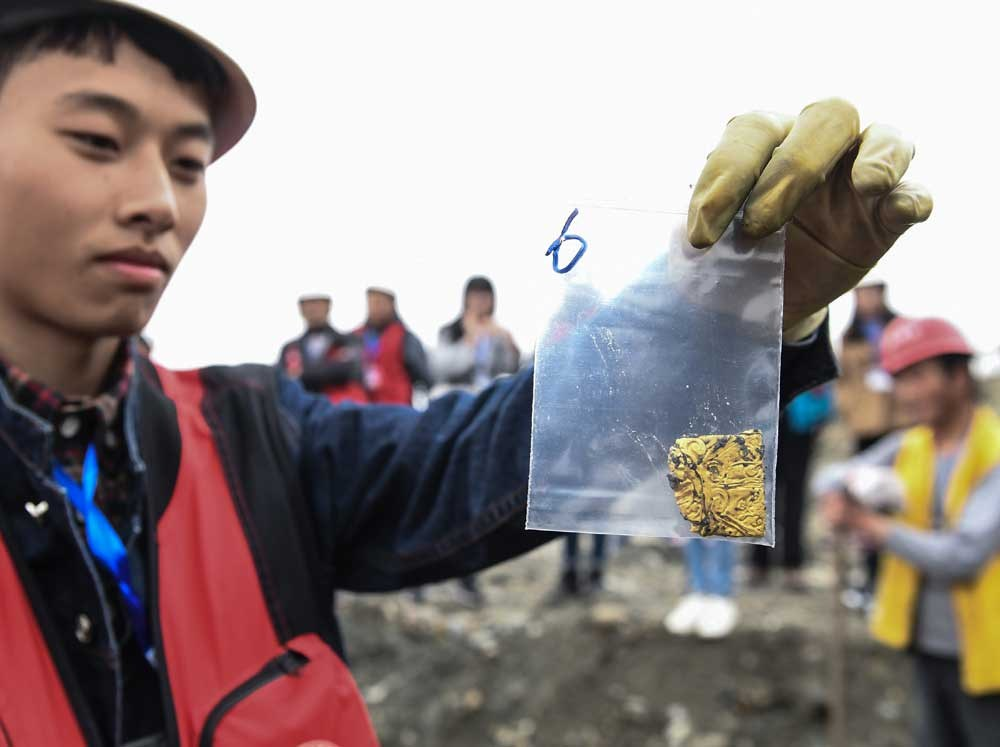 A person involved in excavations shows a gold item unearthed from a site south of Chengdu.