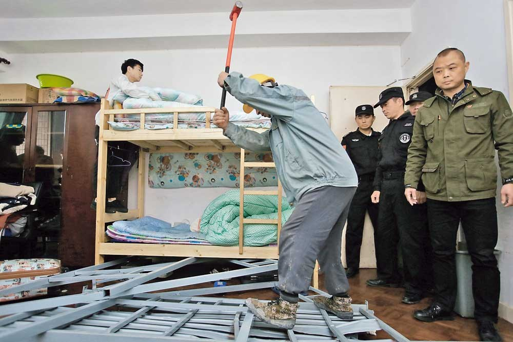 A worker destroys bunk beds in an apartment in Xuhui District yesterday. Officials are cracking down on illegal group leasing following complaints about noise and safety issues.— Jiang Xiaowei