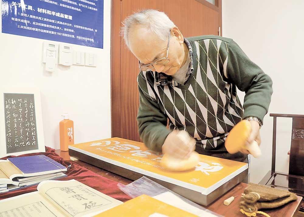 Zhao Jiafu, a master on ancient book preservation and restoration, displaying his skills yesterday at Fudan University. — Dong Jun