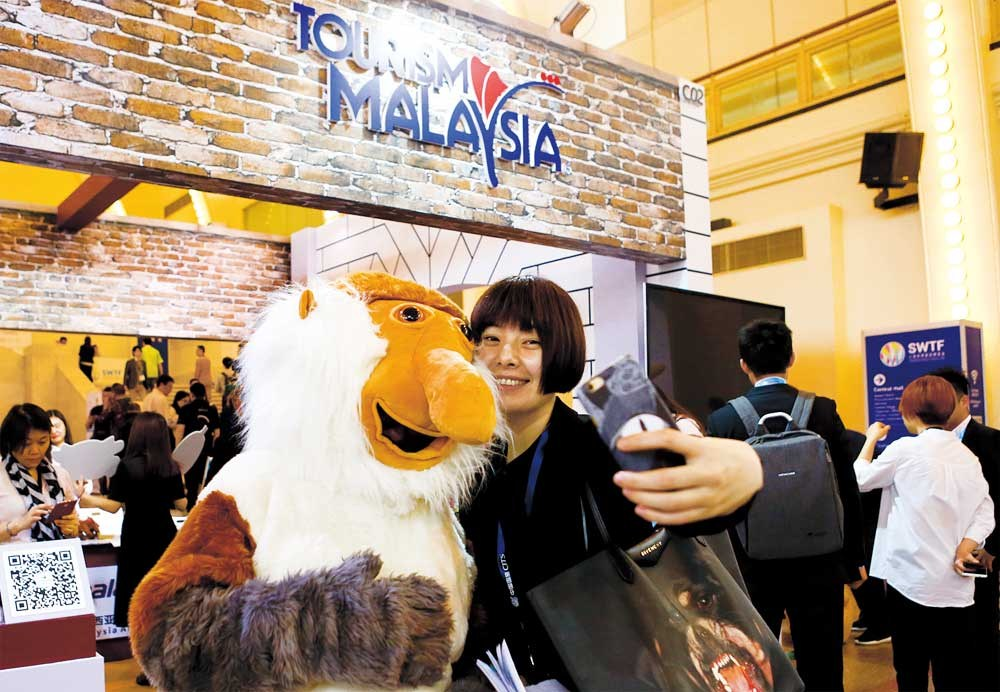 A visitor to Shanghai World Travel Fair takes a selfie with a mascot at the Malaysia stand yesterday. Fifty-two countries and regions are taking part in the event. — Jiang Xiaowei