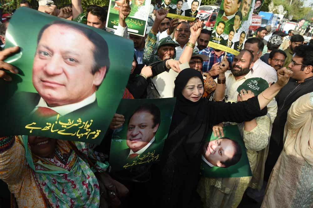 Supporters of Pakistan's ruling PML-N party carry posters of Prime Minister Nawaz Sharif as they hold a celebratory rally yesterday after a Supreme Court verdict in Lahore. — AFP