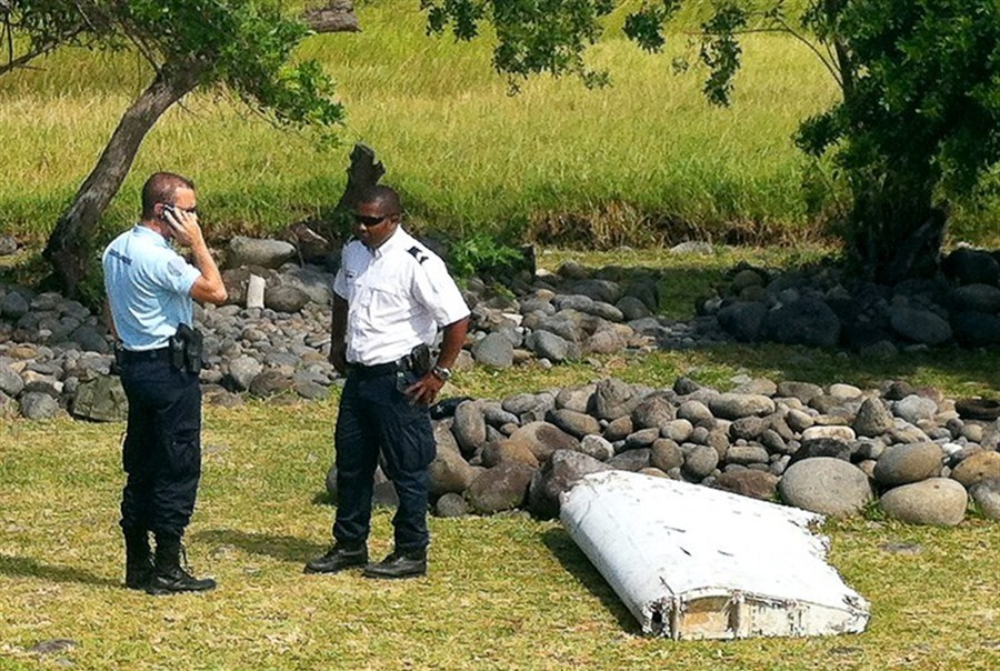 This file photo taken on July 29, 2015, shows a policeman and a gendarme standing next to a piece of debris later identified from missing Malaysia Airlines plane MH370, found on the French Indian Ocean island of La Reunion. -- AFP