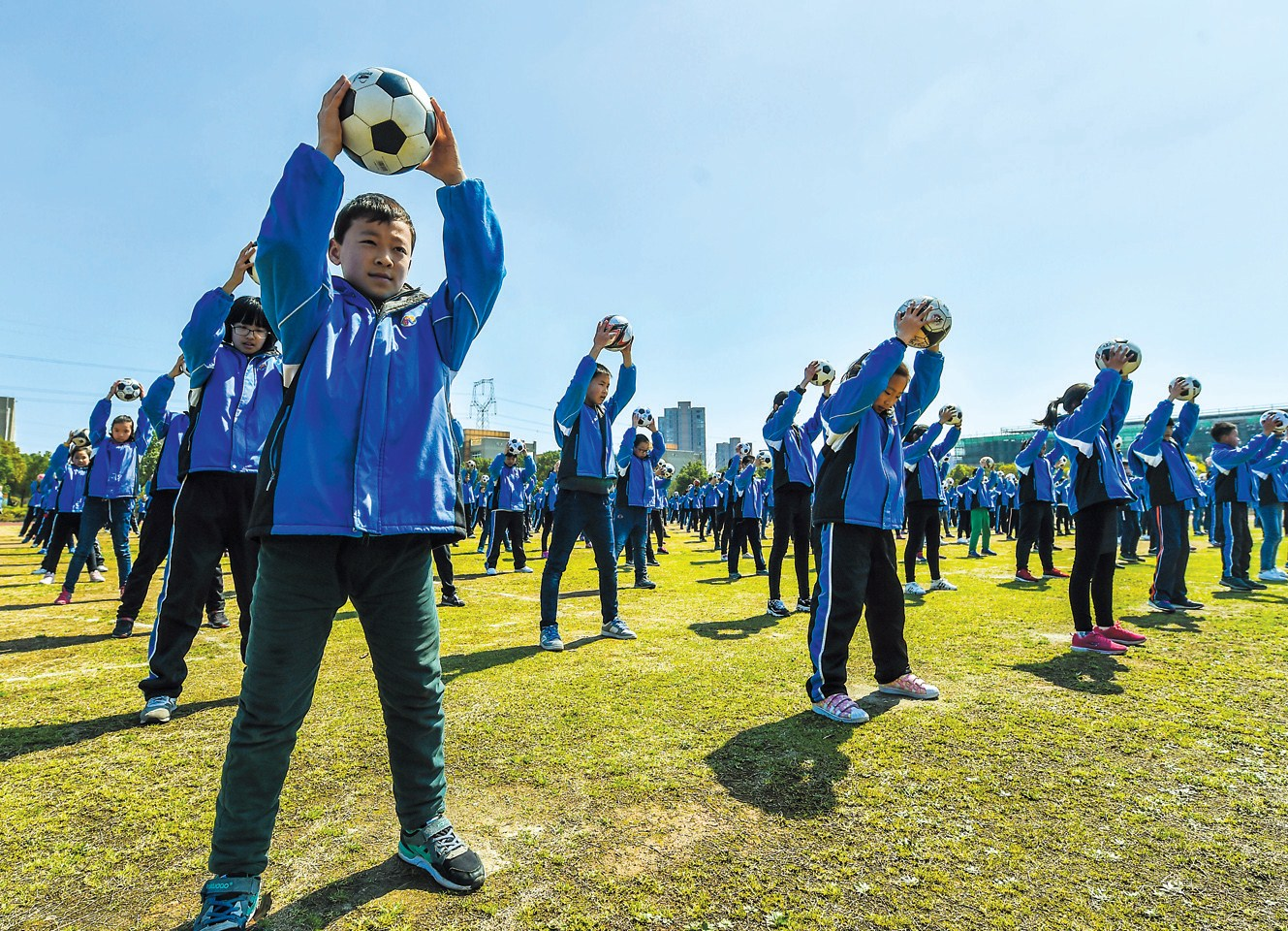 Students at the Changxing County No. 6 Primary School in east China's Zhejiang Province gather together for football drills during class breaks. The school offers professional football course and specializes in training young players for professional teams. — Xinhua