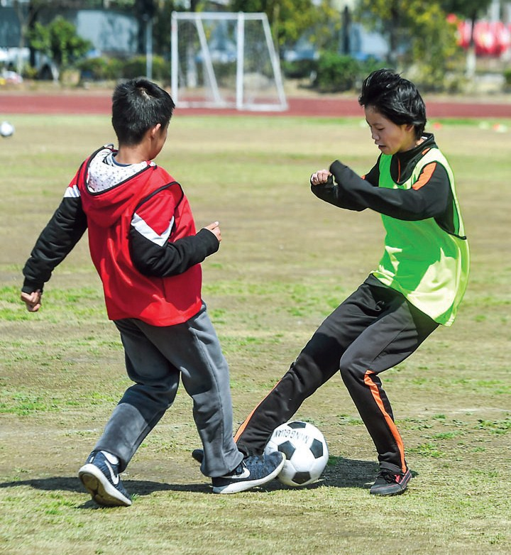 Members of the Changxing County No. 6 Primary School football team play in a match.  — Xinhua