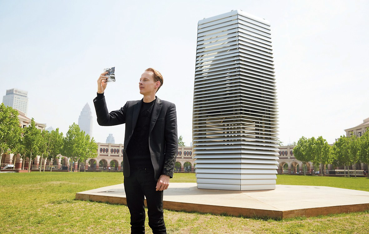 Dutch artist and innovator Daan Roosegaarde, holding a packet of smog particles, stands in front of the smog-free tower in Tianjin.