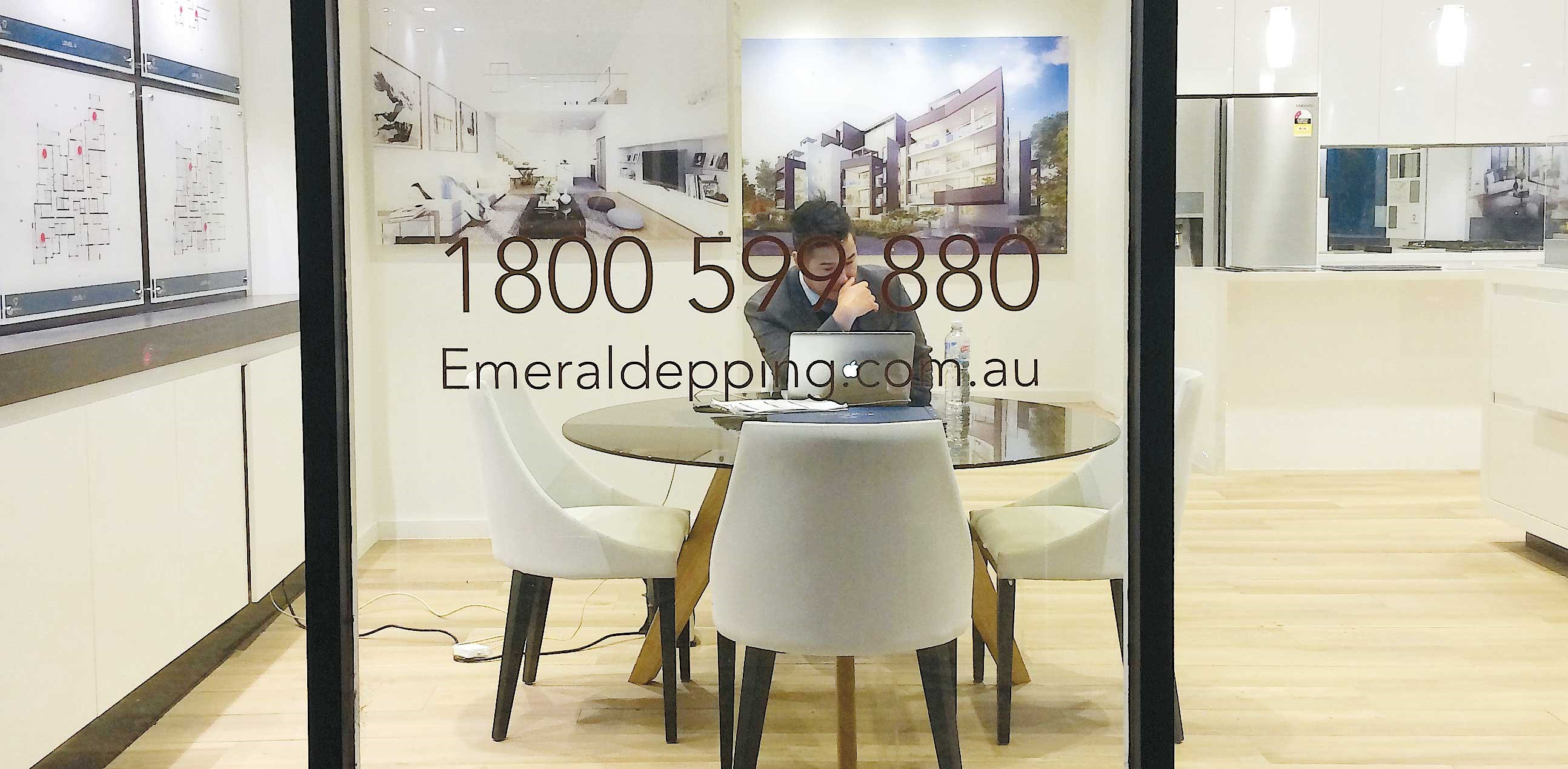 Real estate agent Henry Wong sits in a showroom displaying properties for sale in the Sydney suburb of Epping. — Reuters