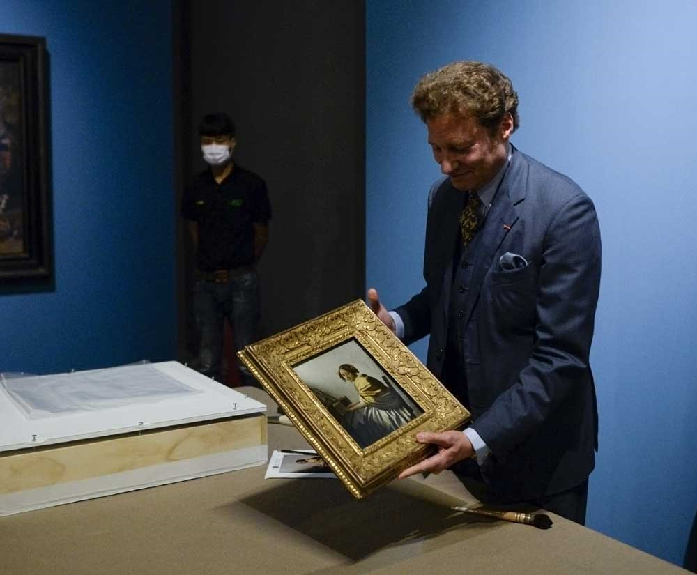 """US art collector Tom Kaplan holds Vermeer's """"Young Woman Seated at a Virginal,"""" one of the masterpieces from the Leiden Collection exhibition at the National Museum in Beijing. China is the first stop on a world tour of the works which will include a showing in Shanghai. — AFP"""