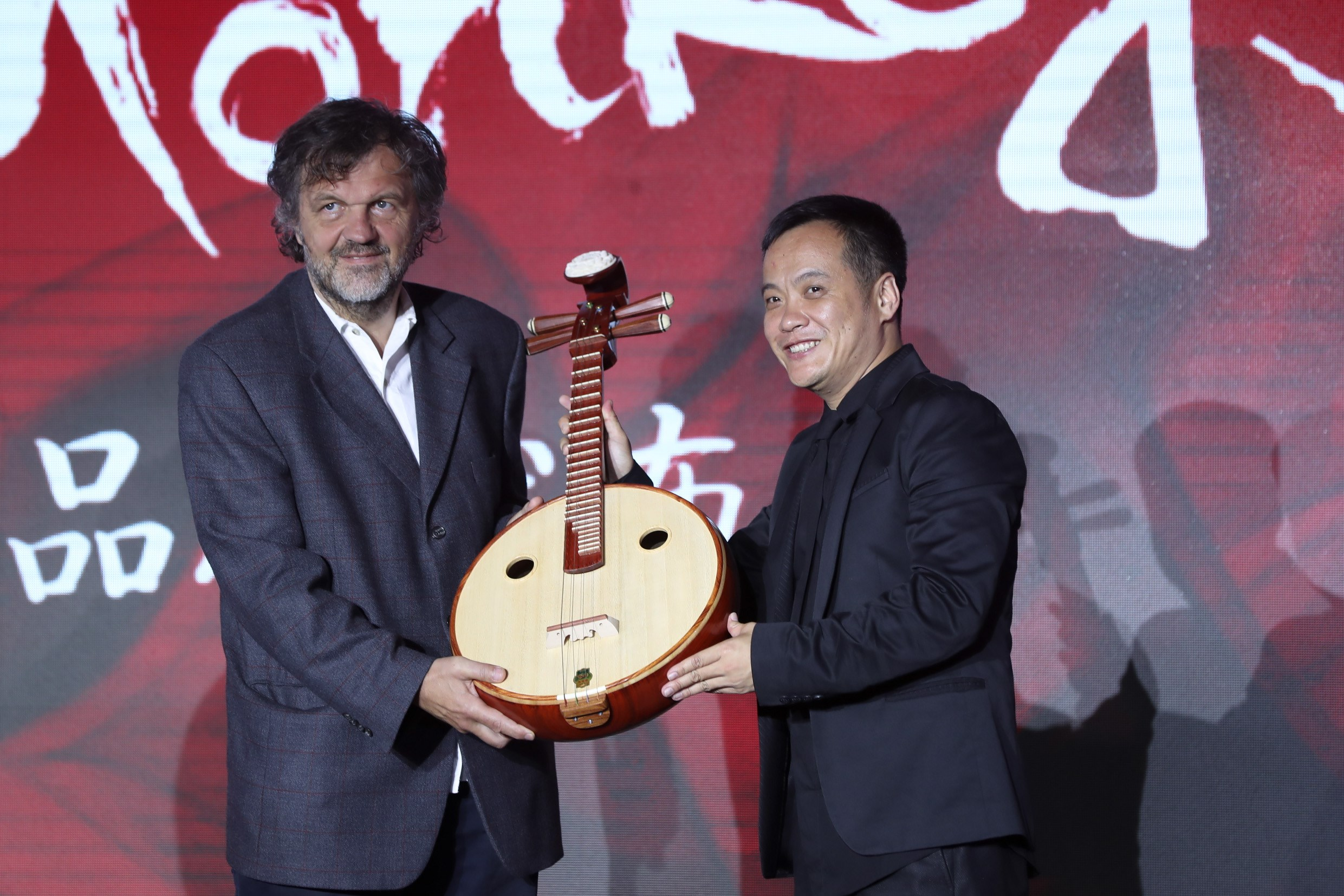 Director Ning Hao (right) gives a ruan, a traditional Chinese plucked string instrument, to Serbian filmmaker Emir Kusturica at a press conference of the Dirty Monkeys Film Corporation. -- Dong Jun