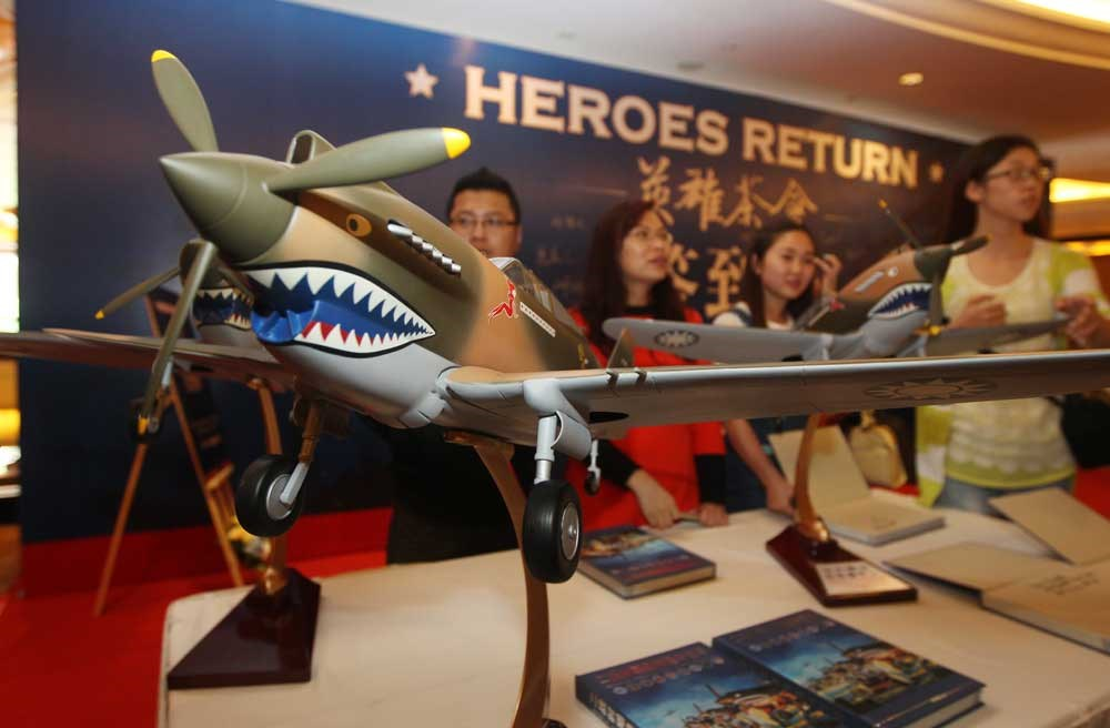 """A group of Chinese visitors gather around a model air fighter used by American """"Flying Tigers"""" during WWII to help China defeat Japanese invaders. — Photo by IC"""