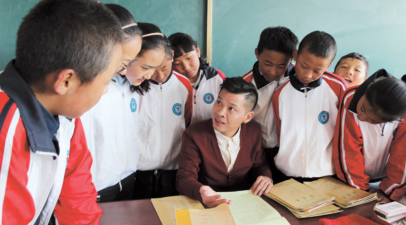 Volunteer teacher Zhang Qingqun discusses classwork with his students at the Shanghai Experimental School in Shigatse.