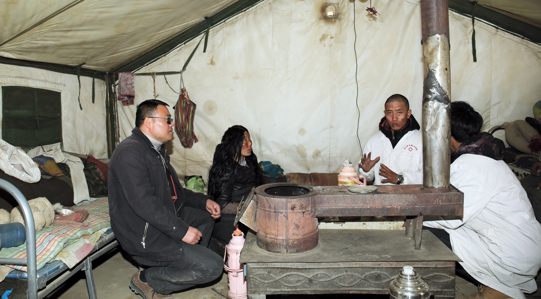 Qian Songjie (left), director of Dingri People's Hospital, visits staff at a tent ward set up to serve patients at a village health center.